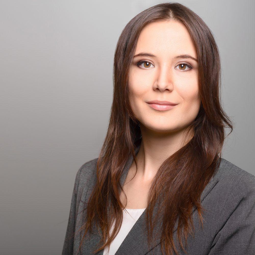Das ist ein Bewerbungsfoto einer jungen Frau, die sich in einem grauen Sakko fotografieren lassen hat, im Fotostudio Harburg, der Profi für schöne Bewerbungsfotos.